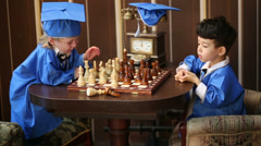 Two thoughtful boys in blue suits of graduates play chess Stock Footage