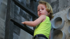Cute little boy climb on ladder in studio with gray walls Stock Footage