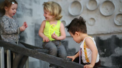 Three happy children sitting on the stairs near gray wall Stock Footage
