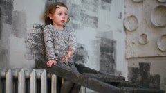 Cute little girl climbing on a ladder in studio with gray walls Stock Footage