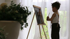 Little boy paints on easel with wooden toy in room near window Stock Footage