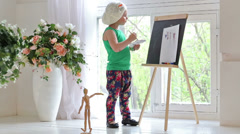 Little girl drawing water color paints on easel near the window Stock Footage