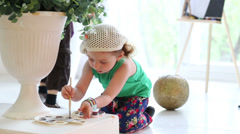 Little girl paints by brush in hand and palette at room with boy Stock Footage