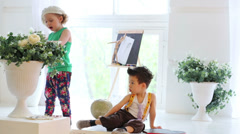 Little girl drawing flowers and boy sits on the floor Stock Footage