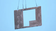 Concrete slab hangs on slings against sky while crane lifts it. Stock Footage