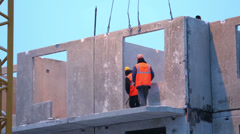 Workers mount concrete slab to proper place at building under construction. Stock Footage