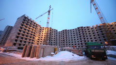 Building works at construction site in winter evening. Stock Footage
