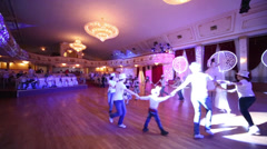 Children and entertainers dance in circle at Surikov Hall Stock Footage