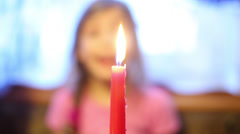 Little girl stands up and blows out burning candle. Stock Footage
