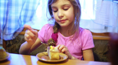 Little girl eats cream from piece of cake sitting at table. Stock Footage