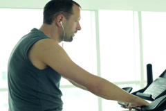 young man ride a stationery bike at the gym NTSC - stock footage