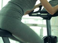 Female legs and ass riding at stationary bike in the gym NTSC Stock Footage