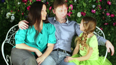 Family of three sits on garden openwork bench and talks. Stock Footage