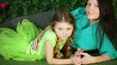 mother and daughter lie on lawn in garden next to verdant fence. - stock footage