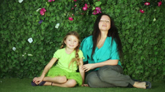 mother and daughter sit on lawn in garden next to verdant fence. - stock footage