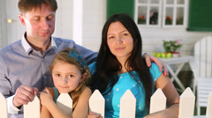 Smiling family of three stands next to cottage white fence. Stock Footage