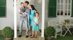 Family stands on porch and then sits down, mother runs off. Stock Footage