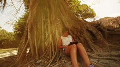 Woman with e-reader under tree - stock footage