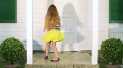 Little girl enters house door, then comes out and stands on porch Stock Footage