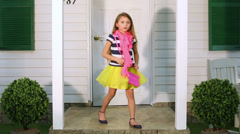 Little girl walks on house porch from one pole to another Stock Footage