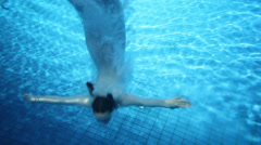 Girl dives into water to bottom and comes back to water surface Stock Footage