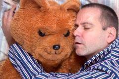 man sleeping in an embrace with a teddy bear - stock photo