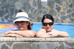 Two sexy women in the pool. focus in the right lady. Stock Photos