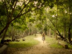 Young Woman Walking Barefoot on Mysterious Path into Enchanted Forest - stock photo