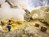 Stock Photo of Sulfur Miner Working at Kawah Ijen Volcano in Java, Indonesia