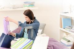 Young happy student girl unpack shopping bags Stock Photos