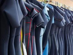 Line of Multiple Hanging Wetsuits - stock photo