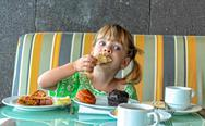 Stock Photo of funny girl eating breakfast