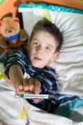 Sick child in bed with teddy bear Stock Photos