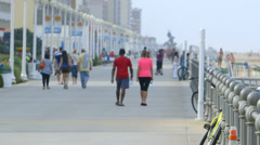 Tourists walk on Virginia Beach boardwalk - stock footage