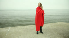 Sad lonely woman in red blanket on the pier. Sea. Stock Footage