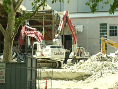TRACTORS TEAR DOWN BUILDING REGUALAR MOTION Stock Footage