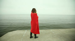 Lonely girl in red blanket on the pier. Full HD with motorized slider. 1080p.  Stock Footage