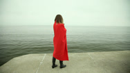 Stock Video Footage of Lonely girl in red blanket on the pier. Full HD with motorized slider. 1080p.
