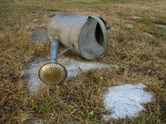 Stock Photo of Empty garden can and parched grass during dry season.