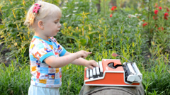 Retro Typewriter Machine in use. Little Girl Writer Printing in a Garden. - stock footage