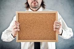 Businessman holding blank bulletin board - stock photo