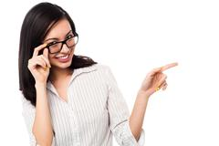 Woman adjusting her spectacles and pointing away Stock Photos