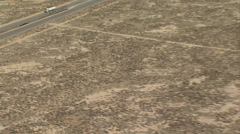 HELICOPTER FLYING OVER PAVED ROAD IN DESERT Stock Footage