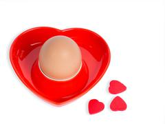 Isolated egg in a red heart-shaped eggcup - stock photo