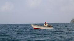 Lone Local Fisherman in Boat Steers Near Stock Footage