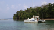 Stock Video Footage of catamaran anchored at exotic tropical beach