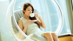 Happy Female Asian Chinese Interior Relaxation Modern Chair Home Coffee Stock Footage