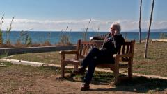 Man sits on bench taking phone call.    Stock Footage