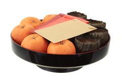chinese new year rice cake, mandarin oranges and red packets - stock photo