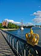 Swedish crown and Stockholm harbour - stock photo